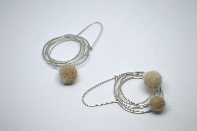 Layers of circles with an earring wire and felted cat hair balls