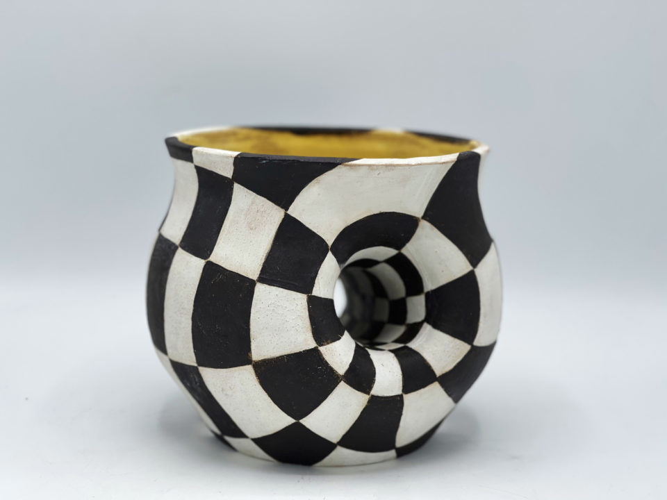 Checkered stoneware pot with tunnel going through it