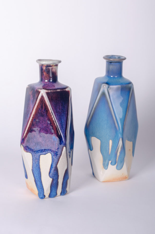 Set of two geometric bottles, one with blue one with purple drippy glaze.