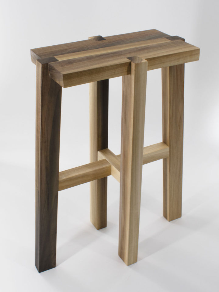 Poplar stool with angled legs, visible joinery where the legs connect to the seat, and a wooden stripe through the seat.