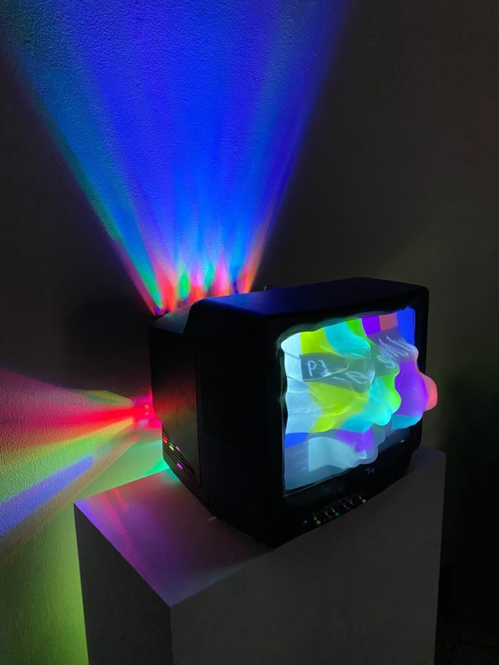 Box TV with light portals coming out of back of TV; abstract TV screen popping out of front of TV; piece sitting on pedestal