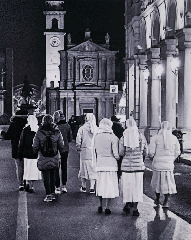 Black and white of people walk down a street in Italy