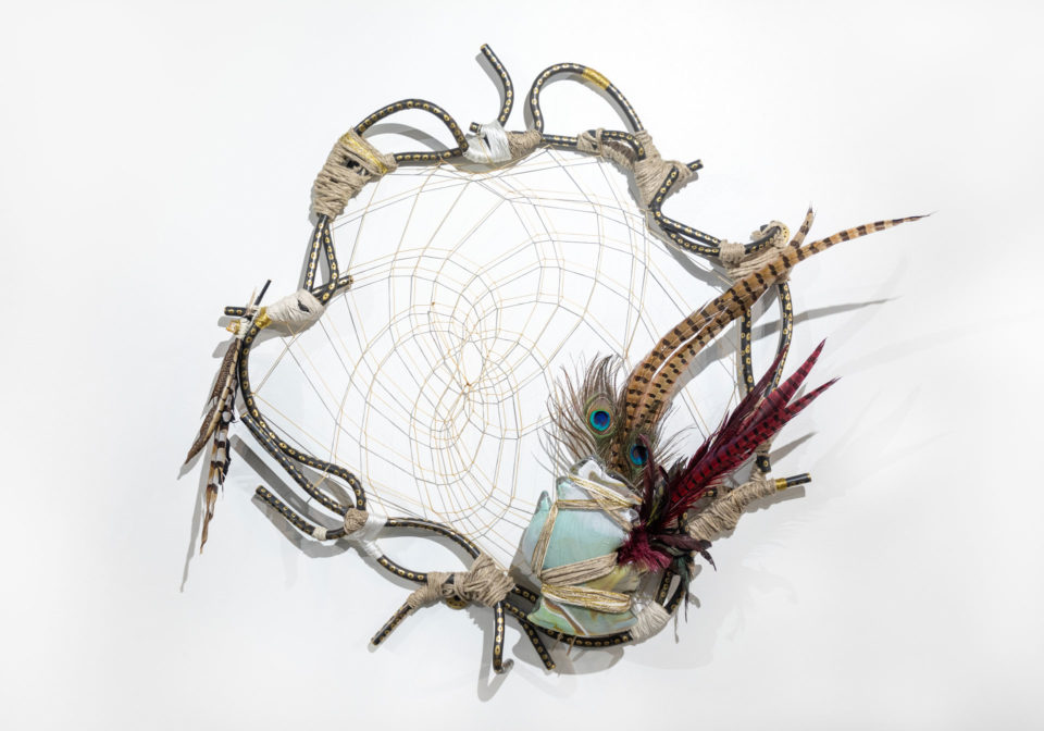 Ornate dream catcher featuring feather and other materials