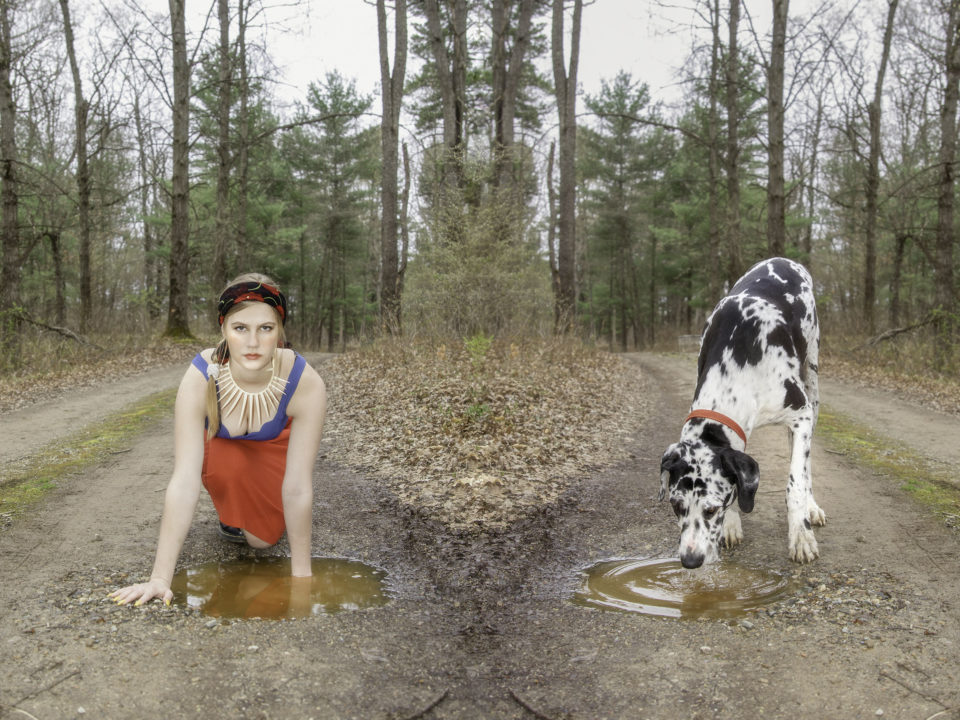 Mirrored image of girl and dog with puddle