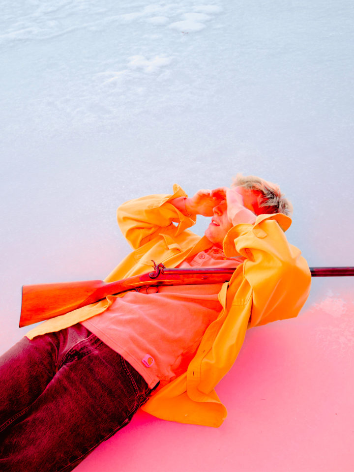 Photograph of a man cast in a pink light covering his face whilst holding a gun, laying on a sheet of blue ice, wearing a yellow jacket.