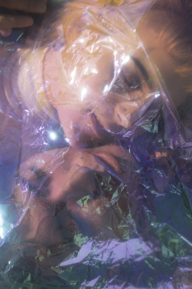 A portrait photograph of two people facing each other under a cellophane haze adding artistic creative color and a futuristic tone.