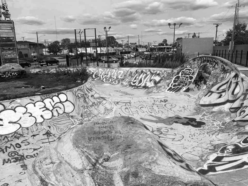 A black and white photograph of a unique skatepark covered in abstract graffiti to display the beautiful landscapes in Detroit.
