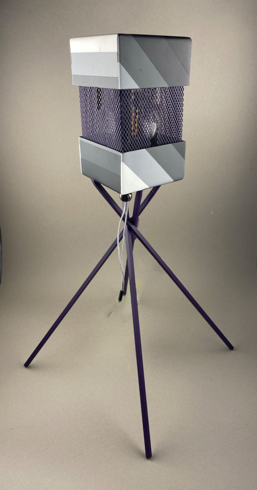 A table top lamp painted in grayscale with purple accents.